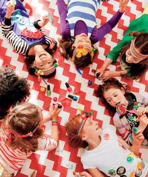 Circle of little girls with rainbow headbands and lollipops playing with nail polish