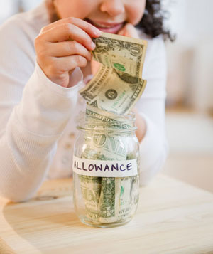 Girl putting allowance into jar