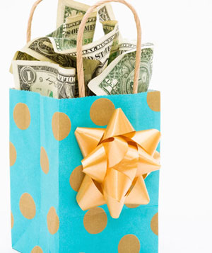 Crumpled US dollar bills in a polka-dot gift bag