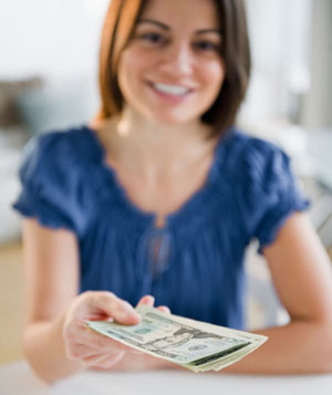 Woman handing over cash, smiling