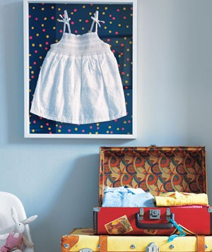 Little white sundress framed on a wall with a polka-dot background