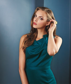 Blonde model wearing teal wool dress with ruffled collar and big gold ring