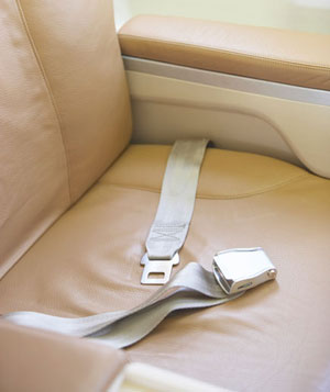 Seat belt across empty seat on airplane
