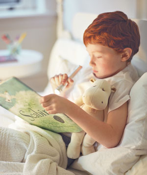 Little boy reading in bed
