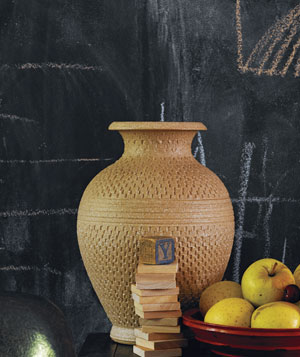 Clay pot next to bowl of yellow apples and stack of thin wooden blocks in front of dark chalk board