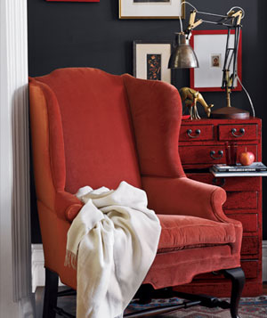 Red velvet arm chair in sitting room with red wooden dresser, patterned rug and framed art on walls