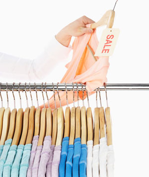 Woman holding t-shirt with sale tag, above clothes rack
