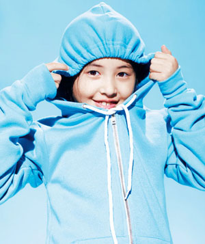 Little girl smiling, peeking through her tightly tied hood