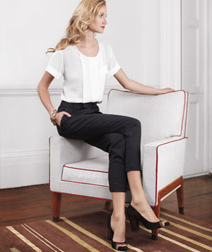 Model wearing cropped black slacks, white blouse and suede heels