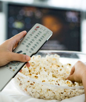Person watching television, holding remote control and bowl of popcorn