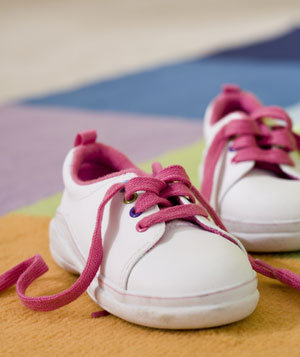 A pair of children's white tennis shoes with pink laces