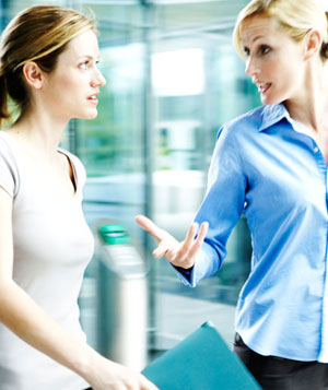Two businesswomen talking, walking through office building