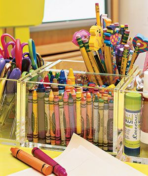 Crayons and pencils stored in a Lucite container