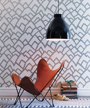 Large black hanging lamp over an orange chair in a room with busy wallpaper and rug