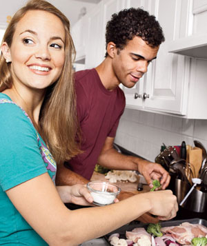 Couple preparing Roasted Chicken and Vegetables