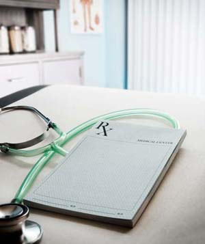 Doctor's notepad and stethoscope on desk in clinic