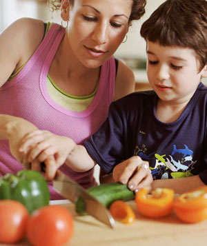 Mother chopping vegetables with son