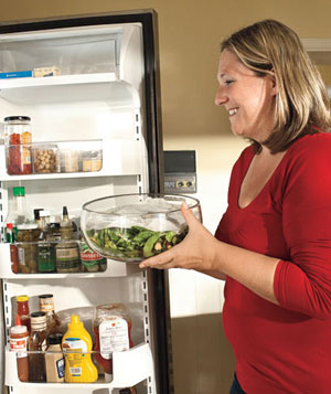 Woman putting leftover salad into the fridge