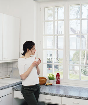 Young woman standing by kitchen window holding cup in both hands