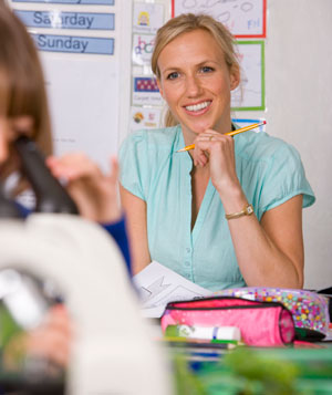 Smiling school teacher supervising children in classroom