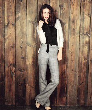 Model wearing tweed plaid pants, white cardigan, black blouse with bow and two-tone suede heels