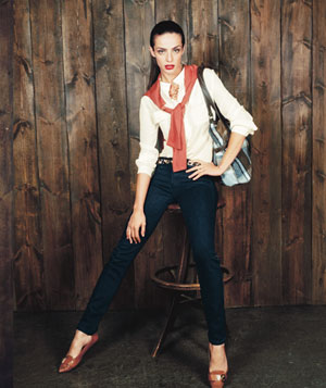 Model wearing white blouse with skinny dark blue jeans, leopard print belt and orange flats