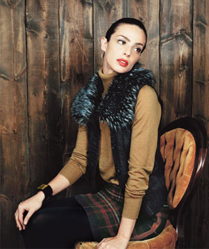 Model wearing faux fur collared vest, beige turtleneck sweater, wool plaid skirt and red lipstick