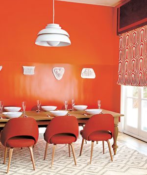 Modern dining room with bright orange walls, chairs and window shade