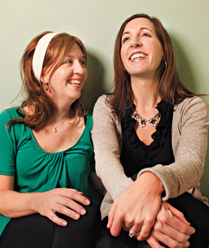Two women sitting together laughing