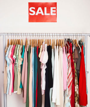 Clothes hanging on rail, sale sign on wall