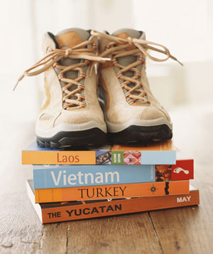 Hiking shoes on top of travel books