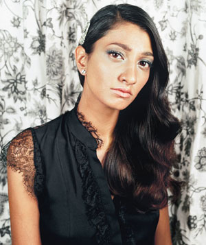 Model wearing black silk blouse with lace trim