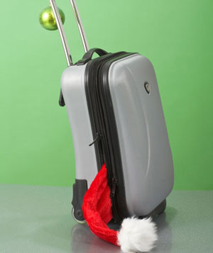 Santa hat poking out of hard-shell suitcase