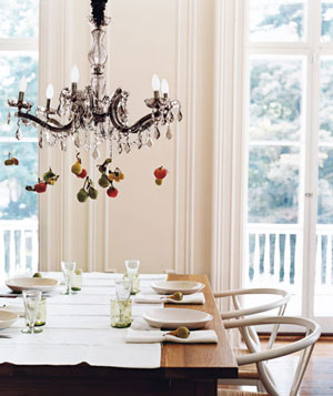 Dining room chandelier with miniature fruit hanging off of it