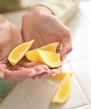 Hands holding lemon wedges
