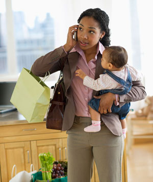 Business woman with grocery bags holding baby and talking on phone