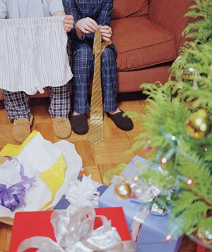 Father and son sitting on couch opening presents in front of a Christmas tree