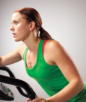 Woman in green tank top using cardio machine