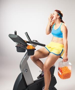 Woman on exercise bike eating junk food