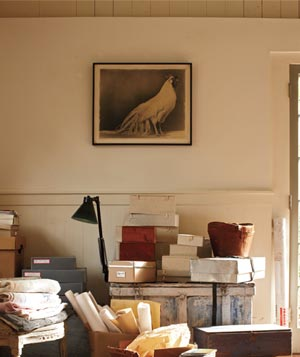 Bright room with piles of boxes, blankets, paper rolls and cds