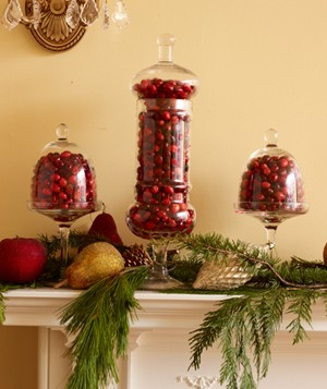 Cranberries in glass urns decorating mantel