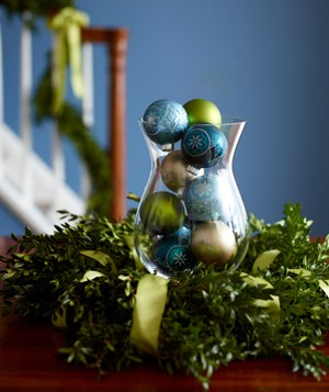 Christmas ornaments in a glass vase surrounded by a wreath