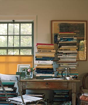 Desk with piles of books on and around it