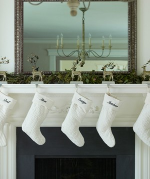 Traditional white stockings with embroidered names hanging from mantel