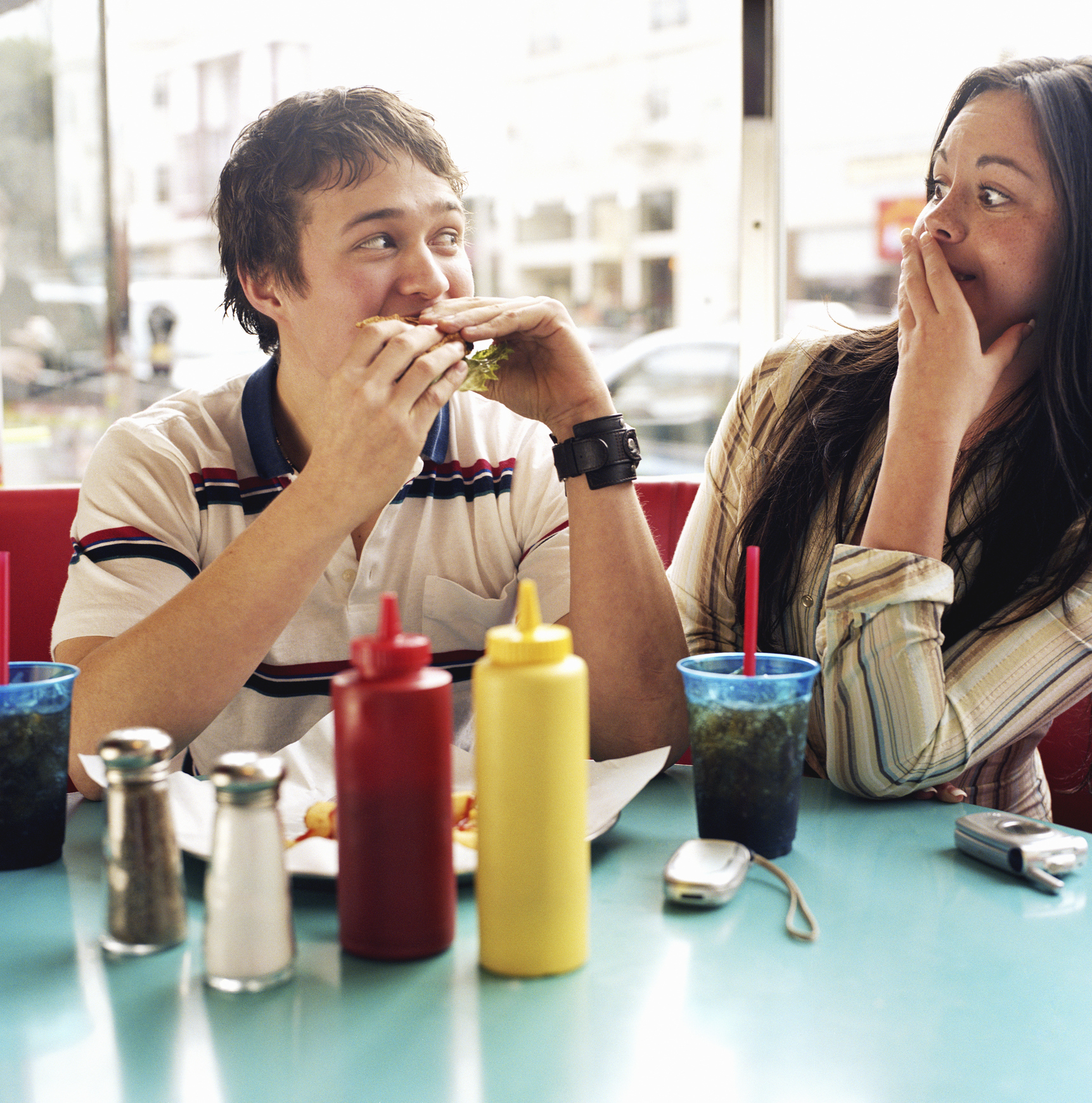 Couple eating burger at diner