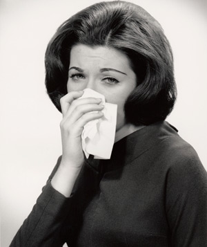 Woman wiping her nose with a tissue