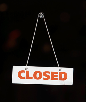 Closed sign hanging over black background