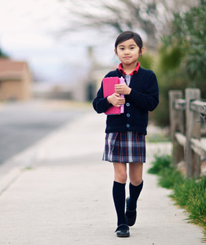 School girl walking down sidewalk