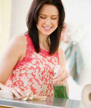 Happy woman cleaning the counter