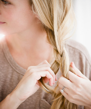 Blonde woman braiding her hair